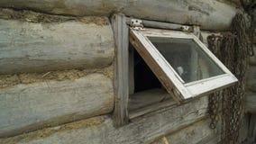 Una pequeña ventana abierta en la casa hecha de remolque de la madera y de la arcilla imagenes de archivo