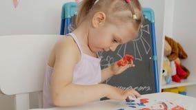 Una peque?a muchacha linda que se sienta en la tabla dibuja en el papel con las pinturas brillantes del finger, sumergiendo sus f metrajes