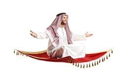 Una persona árabe que se sienta en una alfombra de vuelo Imagen de archivo libre de regalías