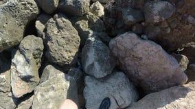 Una persona camina a lo largo de rocas grandes que disfruta de la vista del mar Tiroteo de la primera persona Opinión del mar en almacen de metraje de vídeo