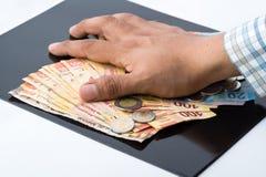 Una persona che accumula tutti i soldi e documenti per il loro proprio beneficio immagini stock libere da diritti