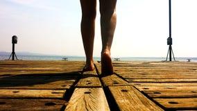 Una persona che cammina su una piattaforma di legno fotografia stock