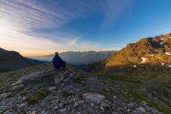 Una persona che esamina alba variopinta alta su nelle alpi Vista grandangolare da sopra con i picchi di montagna d'ardore nel bac Fotografie Stock
