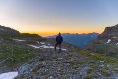 Una persona che esamina alba variopinta alta su nelle alpi Vista grandangolare da sopra con i picchi di montagna d'ardore nel bac Immagini Stock Libere da Diritti