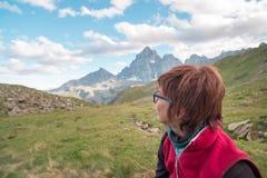 Una persona che esamina la vista maestosa dei picchi di montagna d'ardore il tramonto alto su sulle alpi Ima tonificata e filtrat Fotografie Stock Libere da Diritti