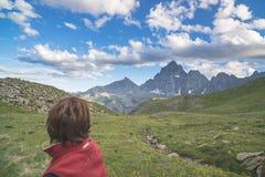 Una persona che esamina la vista maestosa dei picchi di montagna d'ardore il tramonto alto su sulle alpi Ima tonificata e filtrat Immagine Stock