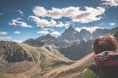Una persona che esamina la vista maestosa dei picchi di montagna d'ardore il tramonto alto su sulle alpi Ima tonificata e filtrat Fotografia Stock