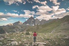 Una persona che esamina la vista maestosa dei picchi di montagna d'ardore il tramonto alto su sulle alpi Vista grandangolare post Fotografie Stock
