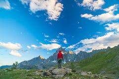 Una persona che esamina la vista maestosa dei picchi di montagna d'ardore il tramonto alto su sulle alpi Vista grandangolare post Immagini Stock