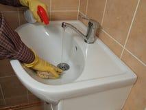 Una persona che pulisce il dispersore della stanza da bagno. Fotografia Stock Libera da Diritti