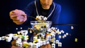 Una persona che si siede davanti ad una ciotola con le pillole sta andando mangiare come un pasto stock footage