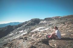 Una persona che si siede sul terreno roccioso e che guarda un livello variopinto di alba su nelle alpi Vista grandangolare da sop Fotografie Stock Libere da Diritti
