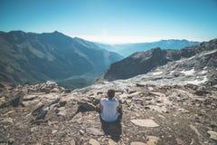 Una persona che si siede sul terreno roccioso e che guarda un livello variopinto di alba su nelle alpi Vista grandangolare da sop Immagini Stock