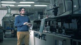 Una persona comprueba el transportador de trabajo en una imprenta almacen de video