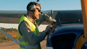 Una persona comprueba un nivel del gas en un pequeño avión Concepto técnico de la condición metrajes
