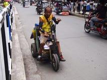 Una persona con i giri e le manovre di inabilità una sedia a rotelle improvvisata Fotografia Stock