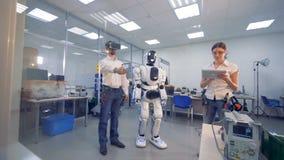Una persona con los vidrios de VR prueba un robot metrajes