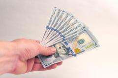 Una persona dà o prende i mille dollari americani Un fan di cento banconote in dollari nella mano sinistra di un uomo Dono o stip fotografia stock libera da diritti