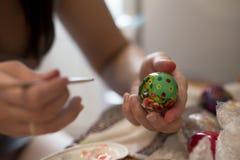 Una persona disegna una spazzola su un uovo di Pasqua con differenti colori immagine stock