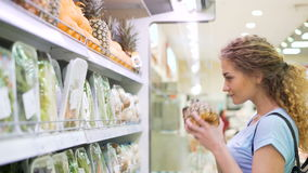 Una persona femenina elige productos en mercado grande almacen de video
