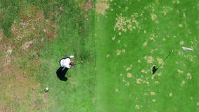 Una persona golpea una bola mientras que juega a golf en un curso metrajes