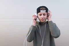 Una persona hermosa y elegante consigue placer de escuchar la música en auriculares en el fondo de una pared ligera Fotos de archivo