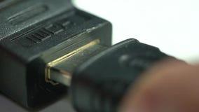 Una persona inserta un conector de HDMI almacen de video