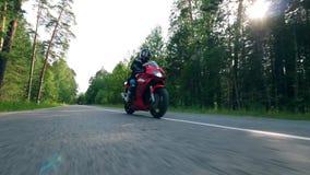 Una persona monta una moto en un camino rápidamente almacen de metraje de vídeo