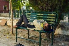 Una persona pobre que toma siesta en banco Imagen de archivo libre de regalías