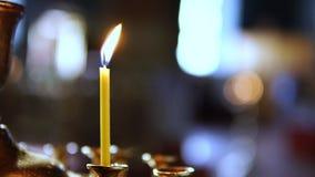 Una persona pone una sola vela al altar en una iglesia ortodoxa metrajes