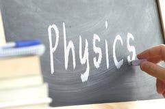 Una persona que escribe la física de la palabra en una pizarra Fotografía de archivo