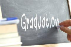 Una persona que escribe la graduación de la palabra en una pizarra Fotografía de archivo