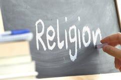 Una persona que escribe la religión de la palabra en una pizarra Fotos de archivo libres de regalías