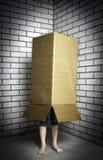Una persona que oculta en una caja Imágenes de archivo libres de regalías