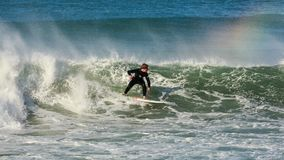 Una persona que practica surf apresura a lo largo de una onda Montaje Maunganui, Nueva Zelandia foto de archivo