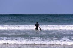 Una persona que practica surf con su tablero que entra el mar foto de archivo