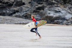 Una persona que practica surf de sexo masculino que corre a través de la playa con la tabla hawaiana Foto de archivo libre de regalías