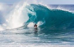 Una persona que practica surf del tablero del cuerpo que monta una onda fotos de archivo