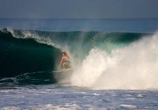 Una persona que practica surf dentro del barril de una onda Fotos de archivo