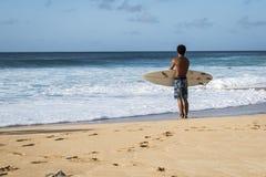 Una persona que practica surf que entra la persona que practica surf del waterYoung está mirando las ondas grandes antes de pract fotografía de archivo