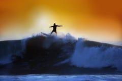 Una persona que practica surf que monta una onda grande en la puesta del sol Fotos de archivo libres de regalías
