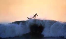 Una persona que practica surf que monta una onda grande en la puesta del sol Fotos de archivo