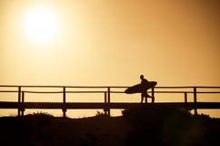 Una persona que practica surf que se ejecuta a la playa Fotografía de archivo
