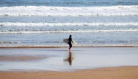 Una persona que practica surf sola que disfruta de su tiempo en la playa durante una mañana soleada de Pascua, Gijón, Asturias, E fotos de archivo libres de regalías