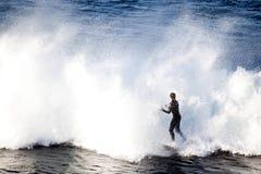 Una persona que practica surf solitaria que aborda ondas enormes Foto de archivo