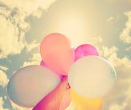 Una persona que sostiene los globos coloreados multi Imagen de archivo libre de regalías
