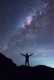 Una persona se está colocando al lado de la mano de la extensión de la galaxia de la vía láctea encendido Imagenes de archivo