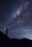Una persona se está colocando al lado del golpe de la galaxia de la vía láctea para arriba en a imagen de archivo