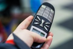 Una persona sottopone un telefono Fotografie Stock Libere da Diritti