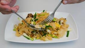 Una persona sta mangiando il gozzo fritto del pesce, cucina tailandese stock footage